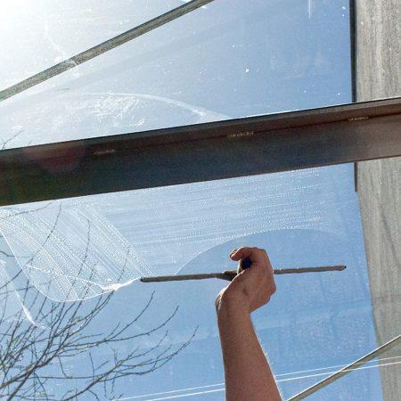 Fensterputzer Regensburg bei der Reinigung einer Überdachung über der Eingangstür.